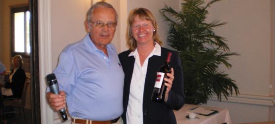 Formann John Nordahl overrekker en flaske rødvin til Ana Nyblom som takk for hennes positive holdning og innsats for Los Vikingos.